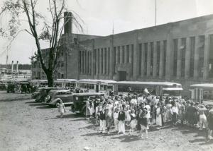 Students gathered along the East side of the building, 1930s.