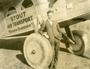 """Stout standing underneath a Stout 2-AT Pullman, """"Maiden Dearborn"""", 1925."""