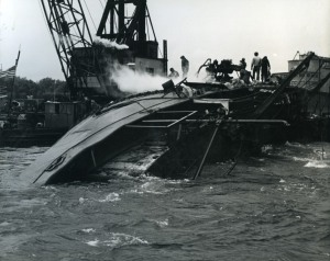 Workers use an old steam-powered pump to suction oil through the side of the capsized SIDNEY E. SMITH, JR.