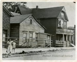 The wooden house on the left stood at 1822 Macomb Street and was occupied by the young Ralph Bunche and his extended family during part of his childhood. The house is pictured here in the early 1950s. The house no longer stands, and the plot on which it stood on is now part of the Dequindre Cut.