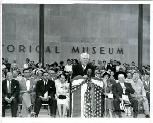 Bunche is pictured here seated between his wife, Ruth H. Bunche, and Michigan Governor G. Mennen Williams, at the dedication ceremony for the Detroit Historical Museum on July 24, 1951.