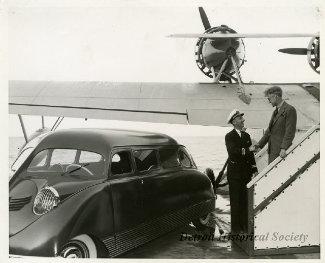 William Bushnell Stout descending the steps of an airplane to a waiting Scarab (1937).